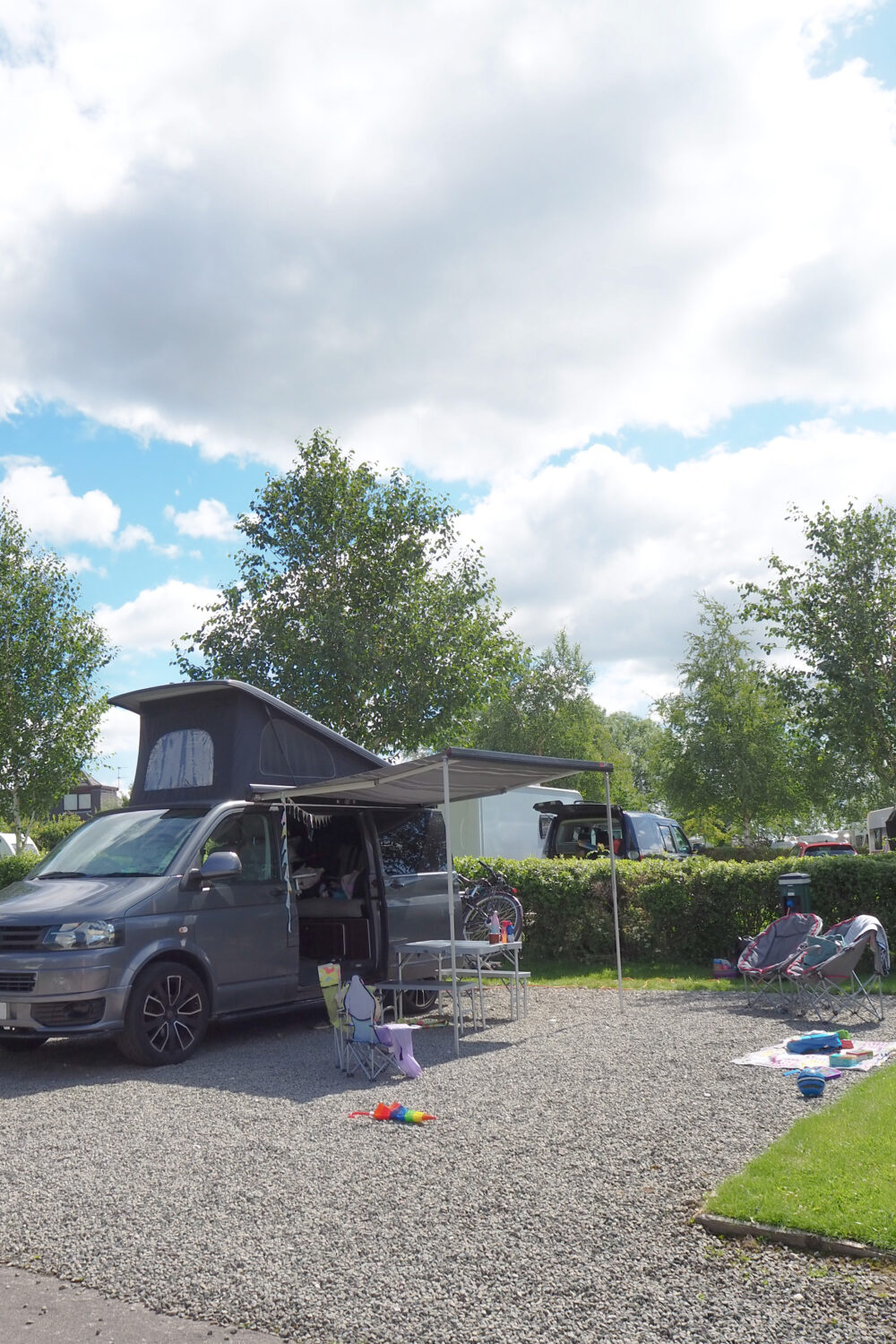 camper set up with a pop top roof, awning and bike rack for a family of five